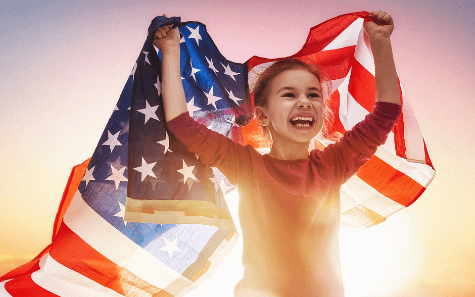 Young girl holding and American flag at dusk.
